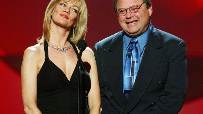 Actor Stephen Furst and Martha Smith, left, speak on stage at The 3rd Annual DVD Exclusive Awards from 2003 in Los Angeles. Furst's son said Saturday that his father died of complications from diabetes. He was 63.