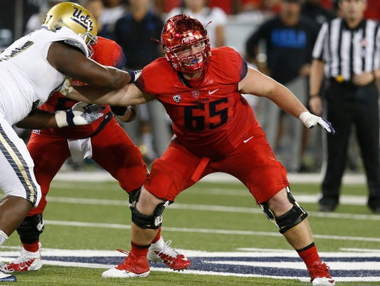 FILE - In this Sept. 26, 2015, file photo, Arizona offensive lineman Zach Hemmila (65) blocks a UCLA player during the first half of an NCAA college football game in Tucson, Ariz. Arizona had to endure one of the most difficult fall camps anywhere, trying to prepare for the season while mourning the death of a teammate. Offensive lineman Zach Hemmila died early in camp, but he has constantly been on the Wildcats' minds as they prepare for their fifth season under coach Rich Rodriguez. The next step is to play a game for the first time since losing their teammate and friend. That chance comes Saturday night against BYU. (AP Photo/Rick Scuteri, File)