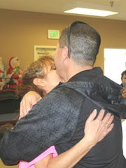 Griseyda Belalcazar hugs her husband after being awarded a thank you from the women she works with at the Mesquite Senior Center.
