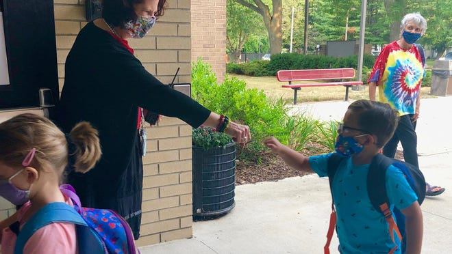 Holland West Elementary principal Kathleen Ramirez greets a kindergarten student Wednesday, Aug. 26, on the first back in the classroom for Holland Public Schools.