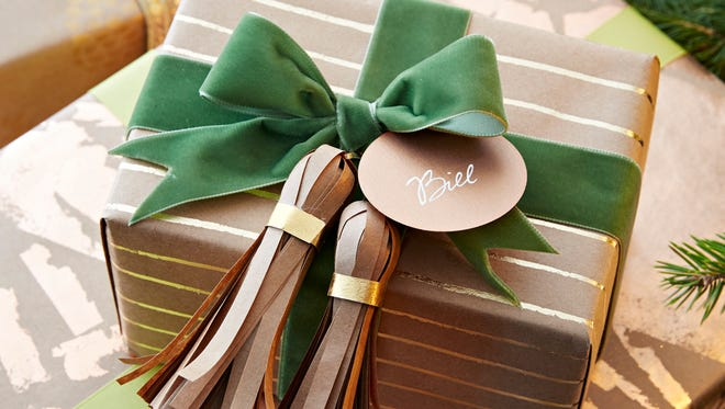 In this photo provided by Better Homes and Gardens, paper tassels adorn a package. Make tassels -- with yarn, ribbon or paper -- as large as possible. That's what makes something look festive and modern.""