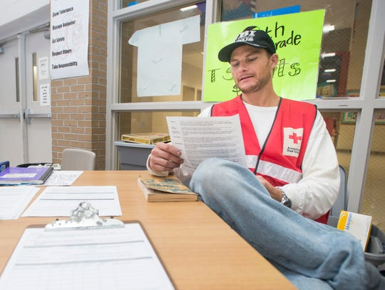 Red Cross volunteer Adam Hoffman looks over paperwork Oct. 7, 2017, as he waits for evacuees at the Jim Bailey Middle School shelter as Hurricane Nate approaches.