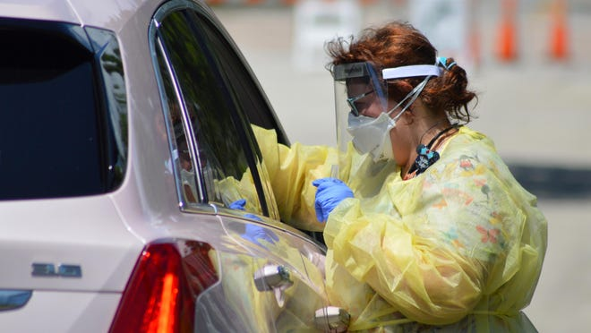 Pam Jones, a registered nurse with Florida Department of Health Volusia County, reaches into a vehicle to conduct a swab coronavirus test earlier this month in Port  t Orange.