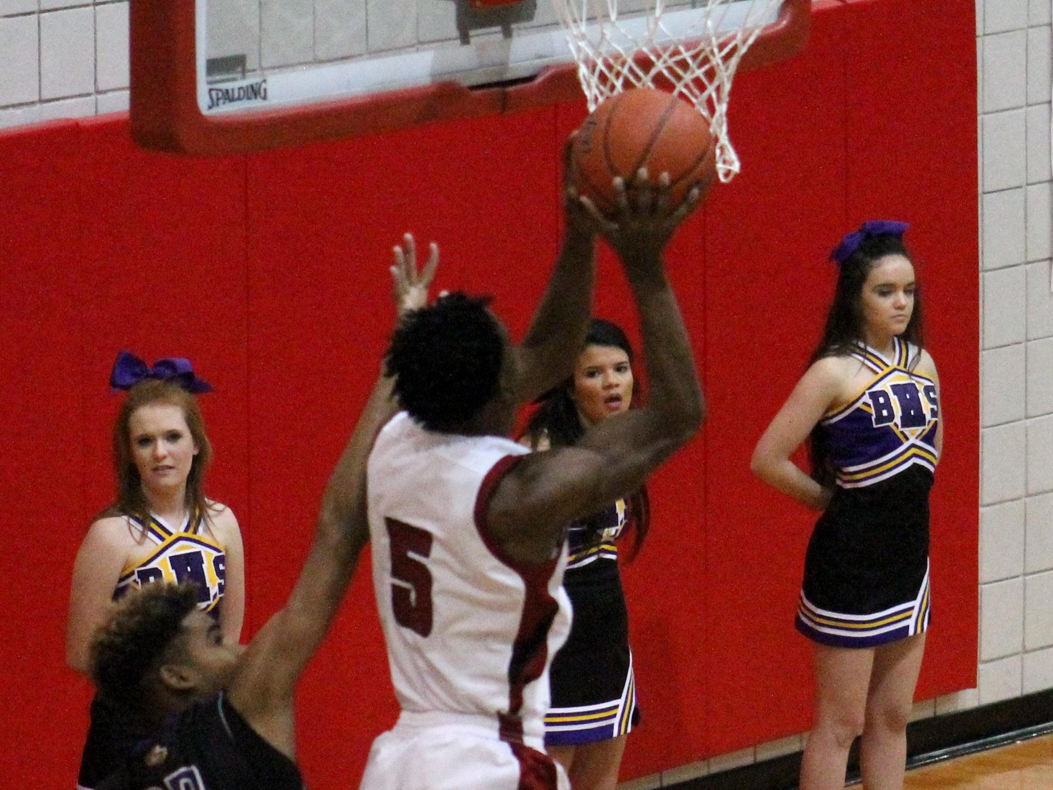 L'Jarius Sneed (5) for Minden goes up for a shot under the basket against Benton's defense during Friday night's boys basketball game at Minden High School.