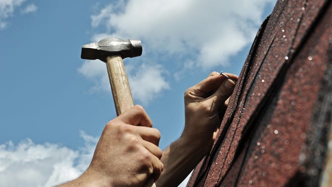 Man holding a hammer and sticking nail into roof