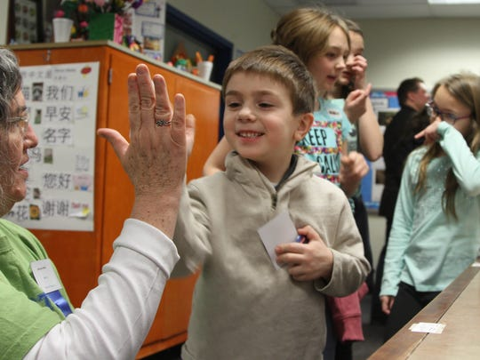 William Evans, 6, gets a high five from Judge Maryrose Walsh, a local school teacher, during the Chester Science Fair at Black River Middle School in Chester Township on Saturday.