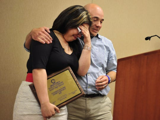 In this 2012 file image, Noelia Lahmann of South Salem High School receives a hug from presenter Todd Bobeda during the Turnaround Achievement Awards at the Keizer Civic Center.