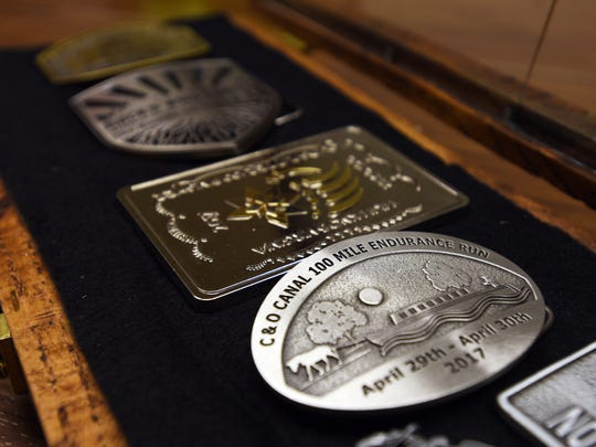 Some of the commemorative belt buckles from Jason Rupe's ultra marathons. Many races award belt buckles to finishers instead of ribbons or medals.