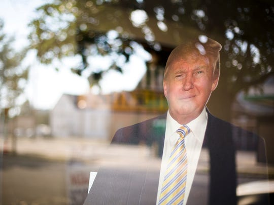 A life-size cutout of Donald Trump stands in the window