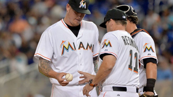 Marlins manager Mike Redmond (right) takes starting pitcher Mat Latos (left) out of the game during the first inning against the Atlanta Braves at Marlins Park.