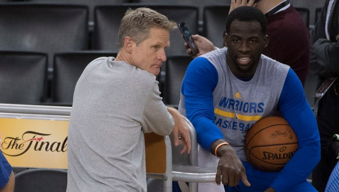 Golden State Warriors head coach Steve Kerr (left) talks to forward Draymond Green (23, right) during the NBA Finals media day at Oracle Arena.