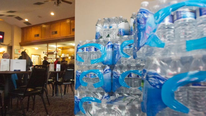 A stack of bottled water stands near the door of the American Legion Devereaux Post 141 in Howell, donated by members to be delivered to residents in Flint.