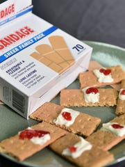 A dab of strawberry jam makes these graham cracker band-aids both used and delicious.
