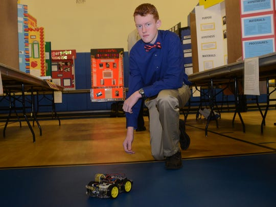 Alexandria Country Day School seventh-grader Aiden Thaxton shows how his science experiment works on Wednesday.