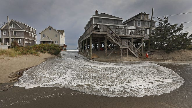 The storm surge pushes water over dunes and between homes at Peggotty Beach in Scituate on Tuesday.