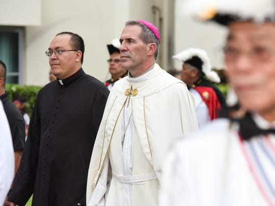 Archbishop Michael Jude Byrnes, center, follows closely