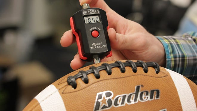 Baden Sports researcher director Hugh Tompkins shows an air pressure gauge reading for a football used in a demonstration in Renton, Wash., Thursday, Jan. 22, 2015. Former NFL quarterback Hugh Millen, who now helps design footballs for Baden, says quarterbacks prefer footballs with less air because of better grip and faster throws. (AP Photos/Manuel Valdes)