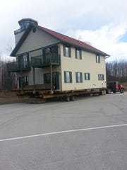 The former Lighthouse Inn being moved for site preparation
