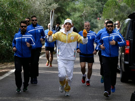 Torch bearer Greek cross-country skier Apostolos Angelis runs with the Olympic flame during the lighting ceremony of the Olympic flame in Ancient Olympia, southwestern Greece, on Tuesday, Oct. 24, 2017. The flame will be transported by torch relay to Pyeongchang, South Korea, which will host the Feb. 9-25, 2018 Winter Olympics. (AP Photo/Thanassis Stavrakis)