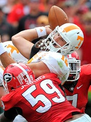 Tennessee quarterback Nathan Peterman (12) is sacked by Georgia outside linebacker Jordan Jenkins (59) on Saturday.