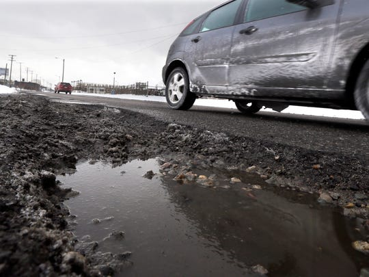 A large pothole is seen on Oakland Avenue in Highland