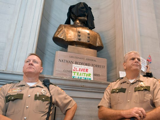 Troopers stand in front of a bust of Nathan Bedford Forrest during a protest at the Tennessee State Capitol Monday, Aug. 14, 2017. A protester covered the bust with a black fabric during the protest.