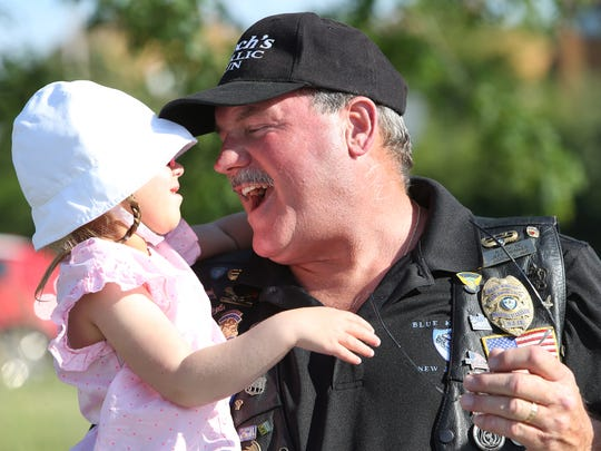 Laura Elise, 5, one of the Garlic Run recipients with Blue Knights Jeff Hunker together before more than 2,000 motorcyclists take the 30-mile ride from Rockaway Township to Newark Wednesday for the 29th annual Gooch's Garlic Run to raise money for local children with physical and catastrophic illnesses. June 15, 2016, Rockaway, NJ