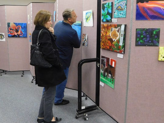 Guests browse the JPII visual art student's creations.