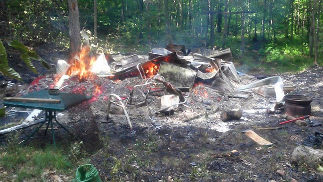 Amber Turner, a neighbor, took this photo of a Milton camp in ashes after the people staying there said they were attacked by a bear and started the fire in an attempt to get away. Police and wildlife officials later said they determined the story was untrue. Tuesday, Lucas Gingras, 28, of Milton was arrested on charges arising from the incident.