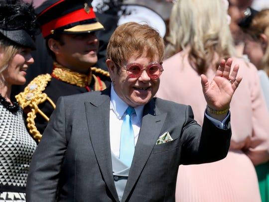 British singer-songwriter Sir Elton John waves as he