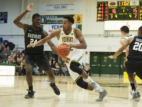 Vermont's Darren Payen (12) drives to the hoop past Harvard's Chris Egi (24) during the men's basketball game between the Harvard Crimson and the Vermont Catamounts at Patrick Gym on Monday night January 2, 2017 in Burlington. (BRIAN JENKINS/for the FREE PRESS)