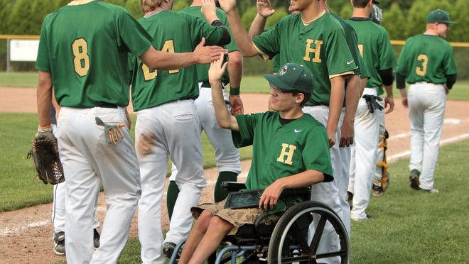 Travis Waker high-fives teammates after a game last month. He kept his teammates loose in the dugout while keeping stats for the Highlanders the last two seasons.