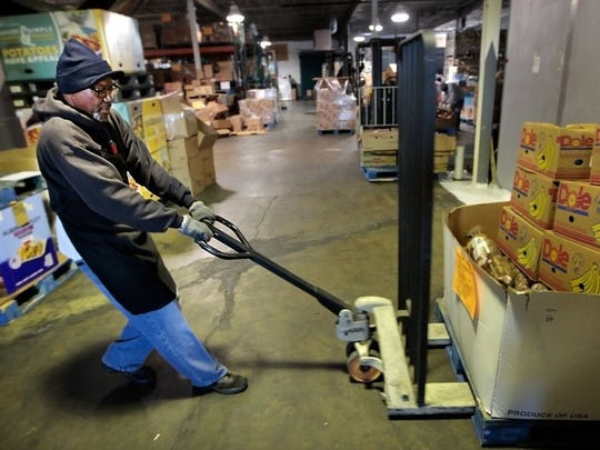 January 6, 2016 - Ulysses Hall  pulls a pallet of fresh vegetables out of the cooler at the Mid-South Food Bank's warehouse.