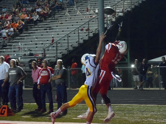 Tioga High School's Trayv'on Culbert (12, right) stretches to catch a touchdown pass against Buckeye High School's Dylan Thomas (24, left) in the Coffee Pot Game last year.