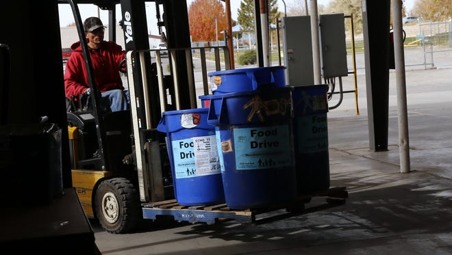 Barrels filled with donated food are moved into ECHO Food Bank Wednesday in Farmington.
