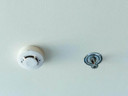 Smoke detector and fire sprinkler on a ceiling.