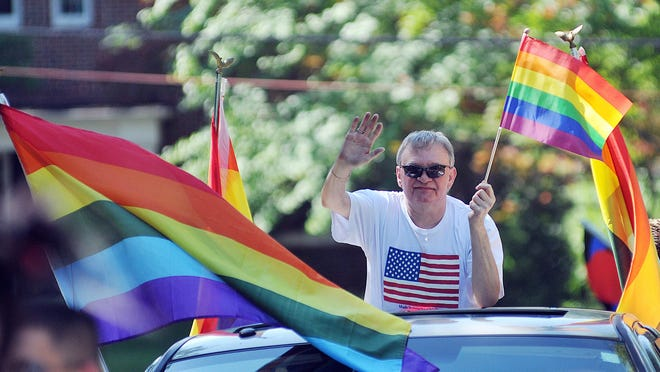 A participant waves during the Mansfield Gay Rights Parade Saturday morning near South Park.