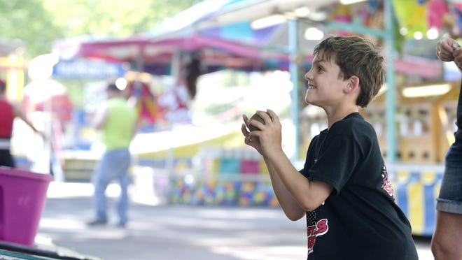 Logan Bauer plays ski ball under the supervision of Sandy Bauer Friday, July 9, during Cootie Days at Dell Rapids City Park.