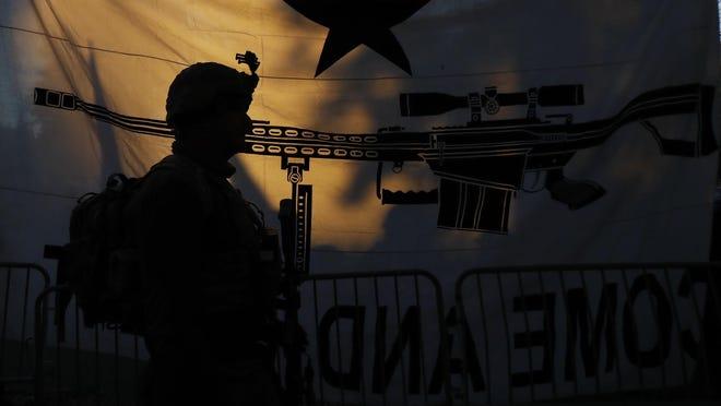 Demonstrators stand outside a security zone before a pro gun rally, Monday, Jan. 20, 2020, in Richmond, Va. (AP Photo/Julio Cortez)