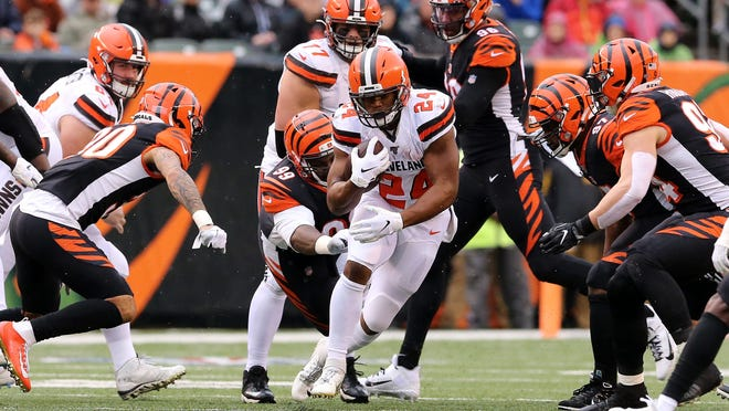 Cleveland Browns running back Nick Chubb (24) carries the ball as Cincinnati Bengals defensive tackle Andrew Billings (99) goes for the tackle in the first quarter during an NFL Week 17 game, Sunday, Dec. 29, 2019, at Paul Brown Stadium in Cincinnati.