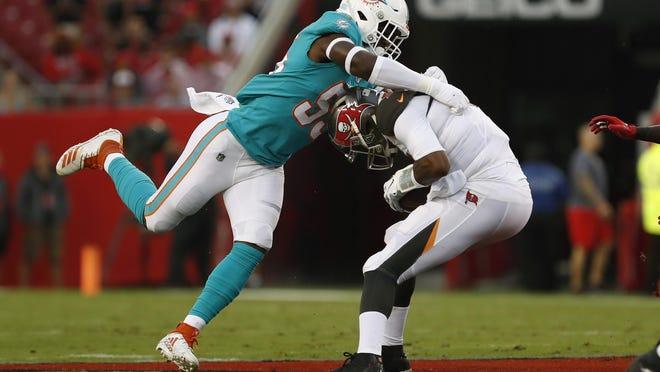Dolphins linebacker Jerome Baker wraps up Bucs quarterback Jameis Winston during a preseason game last season.