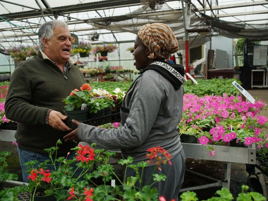 Paul Calistro, executive director of the West End Neighborhood House, picks out flowers with Ashley Hill, 20, who works at Bright Sport urban farm.