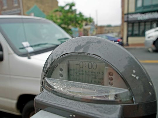 A parking meter on Market Street is left unpaid and a vehicle is ticketed on Wednesday in Wilmington.