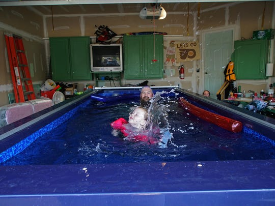 Jon Heap's daughter, Tatum, 2, splashes around the pool with her father, who installed an Endless Pool in his garage to help better the families fitness performance.