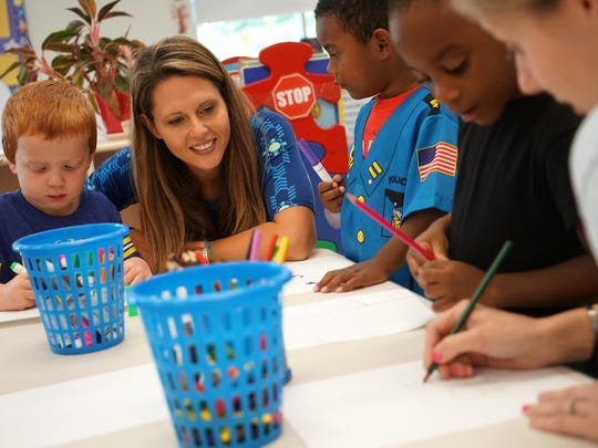 Three-year-old Billy Austin colors a picture next to Jessica Whisler, a consultant for the Department of Education's mental health program, as she make behavioral observations at Brilliant Little Minds.