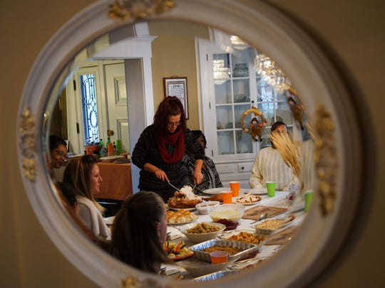 Stacey Garlic, a house manager at the Limen House, carves a turkey she cooked for her fellow residents and alumni in recovery on Thanksgiving.