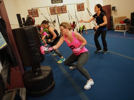 Michelle Oldham, of Unionville, Pa., gives it her all while punching a boxing bag during a small-group training boxfit class at Hockessin Athletic Center. Master personal trainer Dina Saitis instructs the 30 minute class from behind.