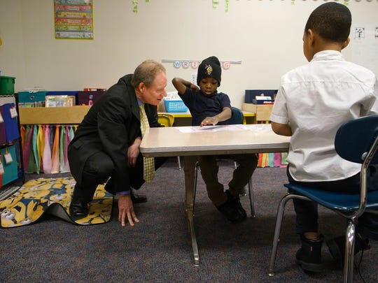 Candidate for superintendent for the Christina School District Gerald (Jerry) B. Wilson squats down to checks out 7 year-old Merv Parker-Arthur, a first grader at Bancroft Elementary School, class work while visiting his reading intervention group class.