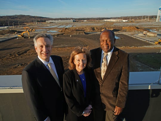 University of Delaware President Dennis Assanis (left), College of Health Science Dean Kathy Matt and Executive Vice President and Treasurer Alan Brangman stand on the roof of the STAR Health and Science building overlooking the construction site of a $40M, 10-story office building to be known as STAR Tower.