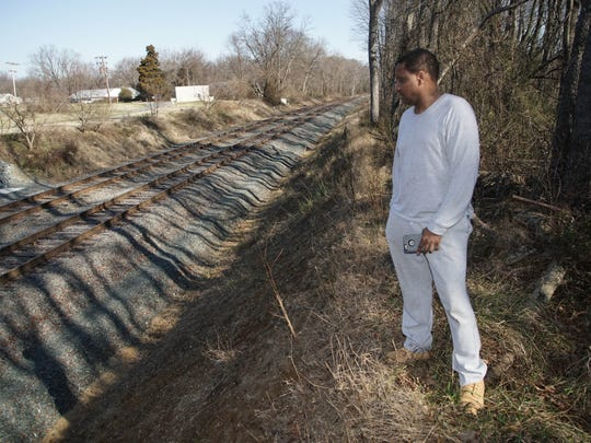 Omar Reid, who has lived in his Mallard Rd. home off Route 13 for over 12 years looks over the tracks that carry oil train pass the back of his property waking his family and bring concern for their safety.